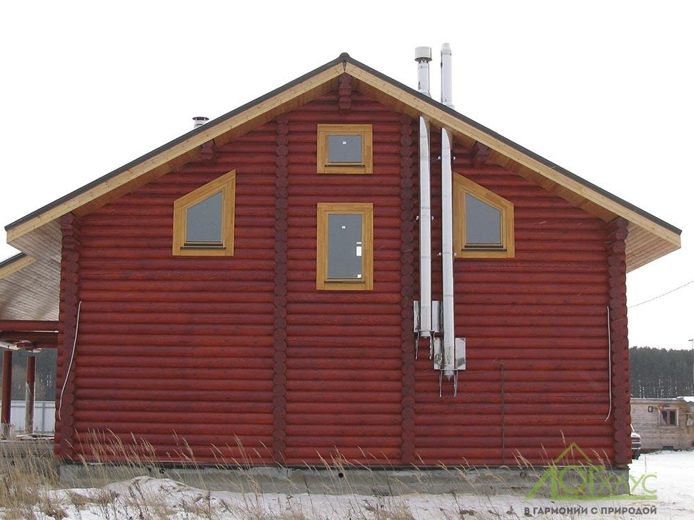Газовый дымоход на фасаде деревянного дома