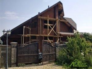 Дом из бревна в процессе покраски