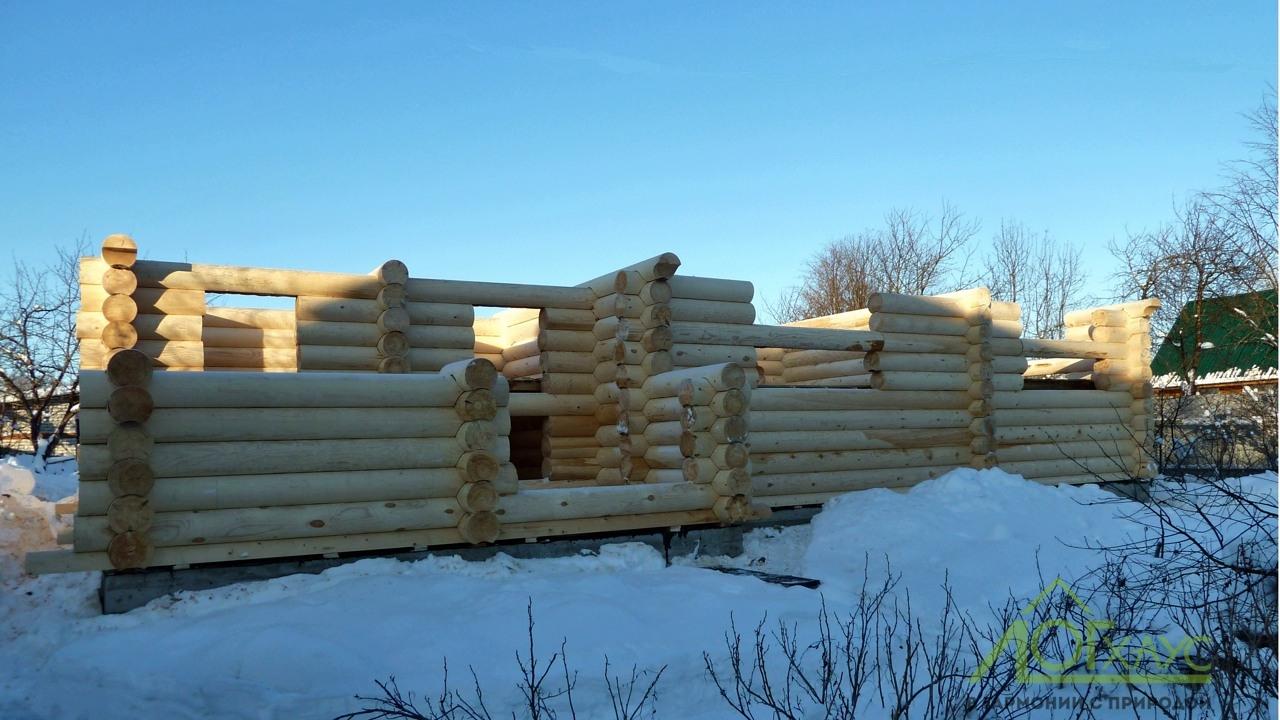 Сборка дома из зимнего бревна на участке клиента