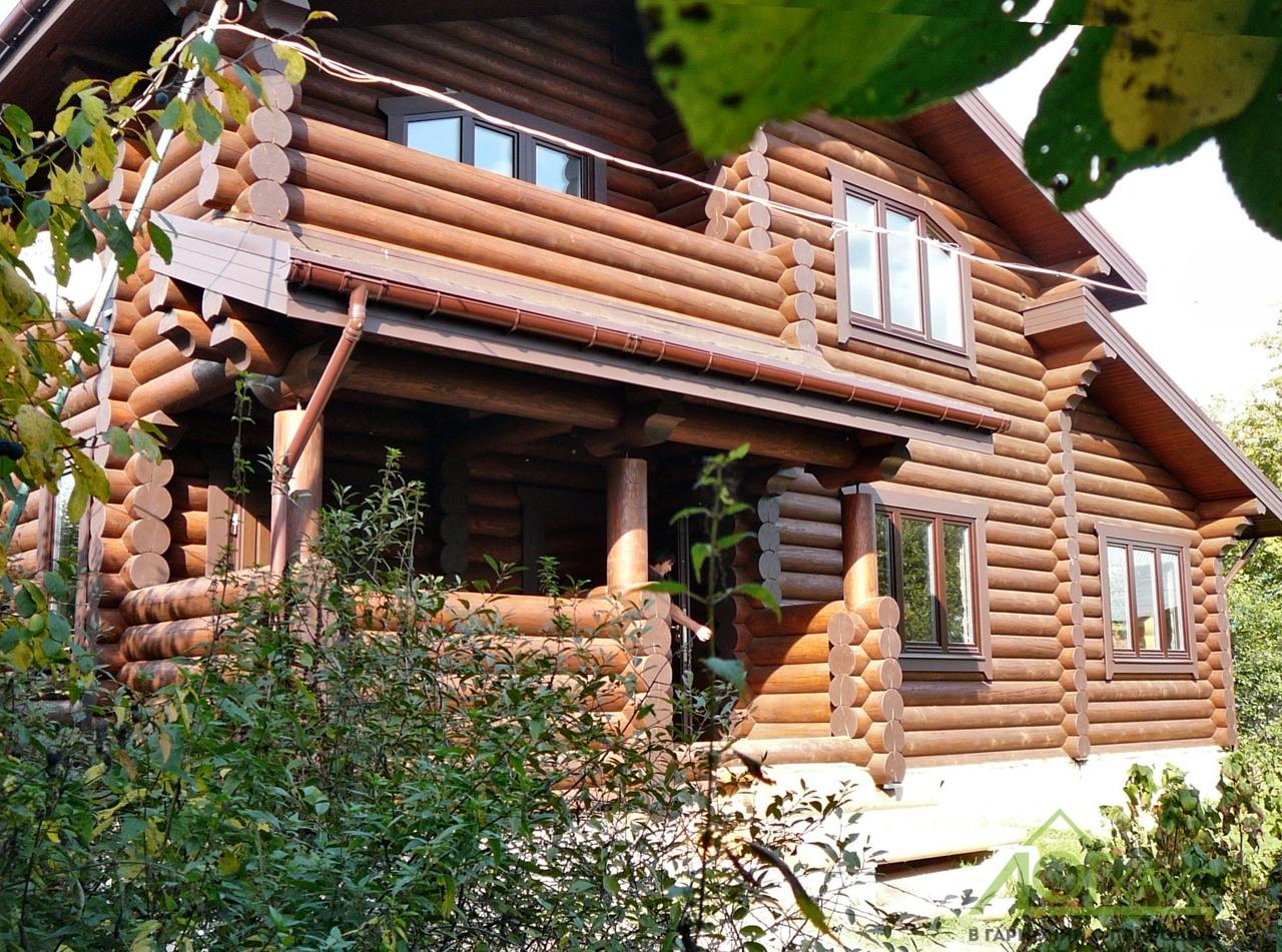 Дом из бревна с террасой и балконом