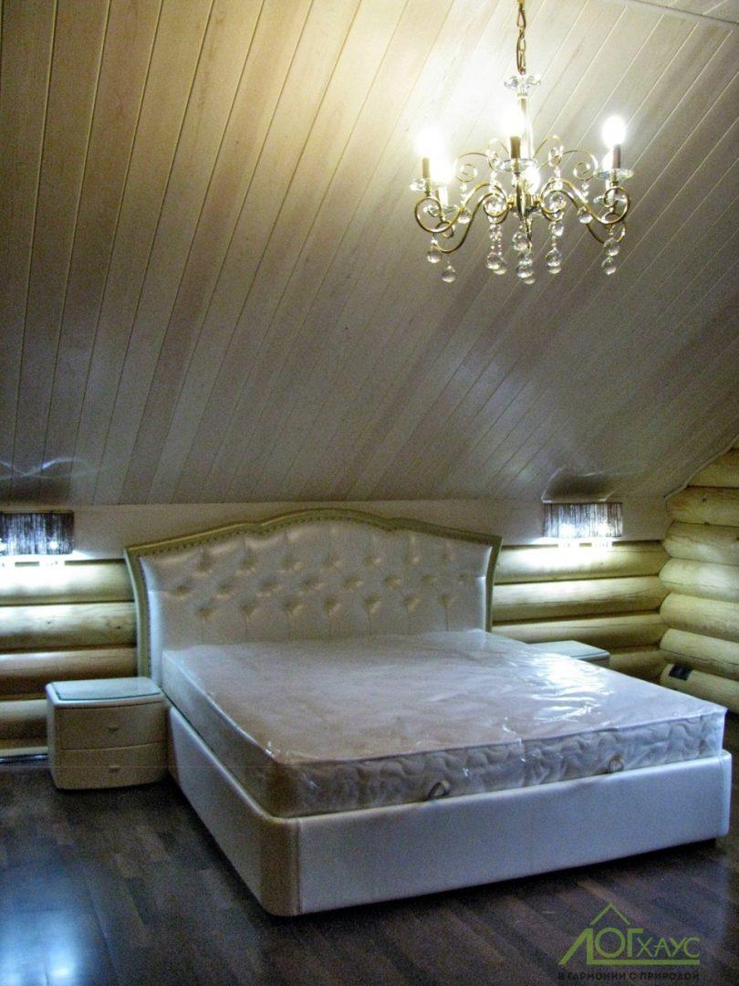 Спальня на мансардного этаже бревенчатого дома