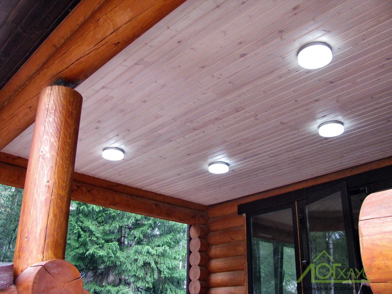Освещение террасы дома из бревна